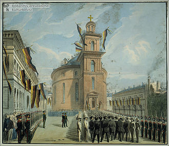 Romanesque church, men marching into it, through a phalanx of uniformed men, houses and church are draped in banners and flags