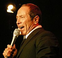 Color bust photo of a man in a tuxedo, holding a microphone.