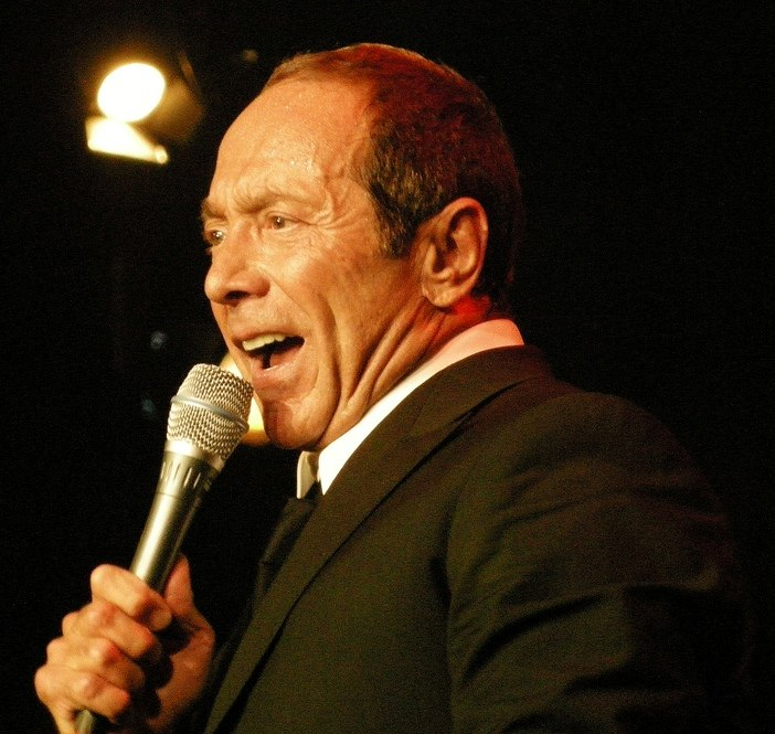 A close image of Anka in a black suit singing into a hand-held microphone with a spotlight in the background