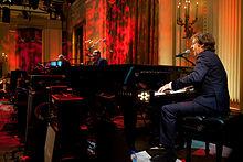 McCartney se apresentando em um piano enquanto cantava em um microfone.