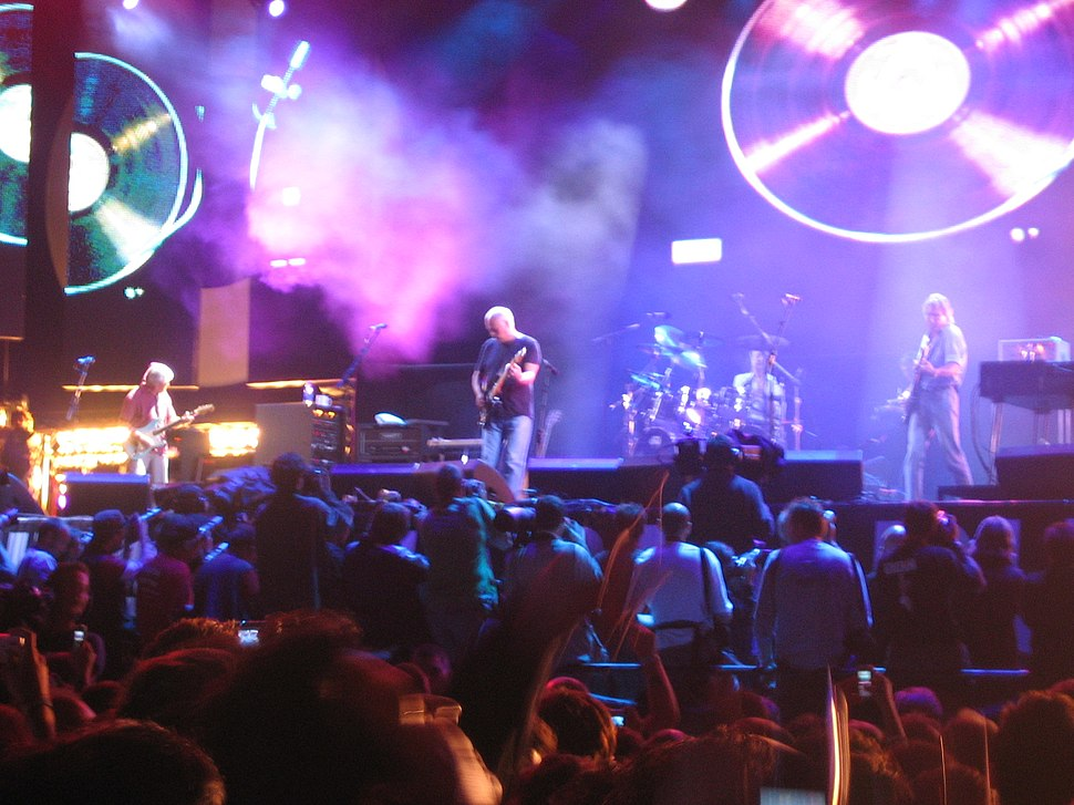 A concert stage lit by purple lighting. Four men are performing on the stage as a crowd stands in front of it. Behind the men are video screens displaying images of vinyl records.