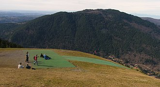 Issaquah Alps - A paraglider takes off from Poo Poo Point on Tiger Mountain. Squak Mountain in background.