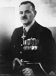 Half-length portrait of a moustachioed man in senior military uniform. He is wearing a group of ten military medals on his breast, with another around his neck and is grasping a sword.