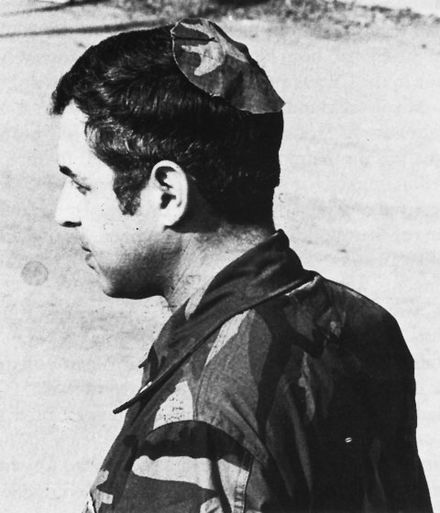 Jewish chaplain Rabbi Arnold Resnicoff wears a kippah/yarmulke made from a piece of a Catholic chaplain's camouflage uniform after his own head covering had become bloodied when it was used to wipe the face of a wounded marine during the 1983 Beirut barracks bombing. Resnicoff BeirutKippa.jpg