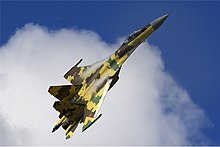 Jet aircraft with yellow, tan and green colour scheme performing aerial display.