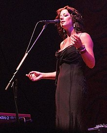 Middle-aged woman with medium-length brown hair wearing a low-cut evening dress while singing into a microphone with her eyes closed.