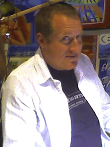 A bust photograph of a middle-aged caucasian man with short hair. He is wearing a white dress shirt over a black t-shirt. He is turned at a 45 degree angle away from the camera, but his eyes point directly at the photographer.