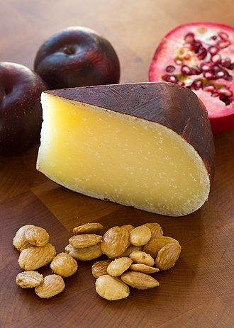 Monterey Jack - A wedge of Dry Jack cheese, shown with plums, pomegranate and roasted almonds