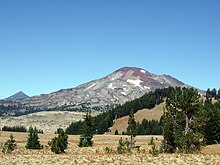 South Sister, which features patches of snow and ice, can be seen above a plain. Forest is visible in the foreground.