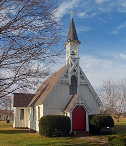 A white church with vertical siding, decorative woodwork on the roofline of its steeply gabled roof, and a red door in front, topped with an open belfry.