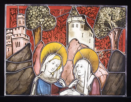 "Part of German panel of 1444 with the Visitation; pot metal of various colours, including white glass, black vitreous paint, yellow silver stain, and the ""olive-green"" parts are enamel. The plant patterns in the red sky are formed by scratching away black paint from the red glass before firing. A restored panel with new lead cames. Stained Glass Panel with the Visitation MET MED700.jpg"