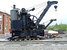 A railway-mounted steam crane, with a vertical boiler mounted at the rear of the crane platform.