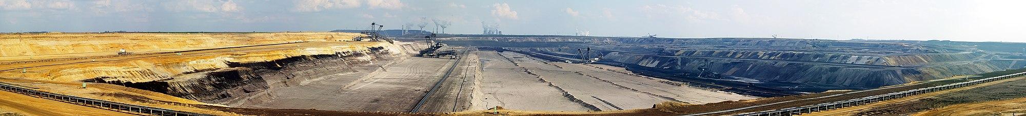 Panoramaaufnahme vom Tagebau Garzweiler mit diversen Baggern im Einsatz und den Kraftwerken in Grevenbroich-Frimmersdorf (links) und -Neurath sowie Bergheim-Niederaußem (rechts) im Hintergrund