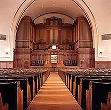 Facing the viewer are the backs of many rows of pews, with a carpeted aisle in the center. At the front of the room is a very large, wooden structure, which fills the far wall.