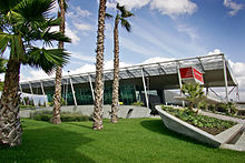 Airport terminal, with four trees in the foreground