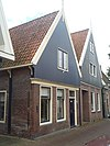 foto van Eenvoudig huis met houten topgevel op geprofileerde lijst