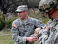 U.S. Army Spc. Jonthomas C. Oudyk, left, a practical nurse with the 349th Combat Support Hospital, demonstrates the application of a pressure bandage on Sgt. Carlos S. Kaiser, during Warrior Exercise 91 13-01 130314-A-VX503-043.jpg