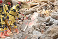 U.S. military service members, dressed in protective gear, cut through metal debris on a simulated rubble pile during a joint training exercise conducted by the U.S. Air Force and the U.S. Army involving 080626-A-BB257-083.jpg