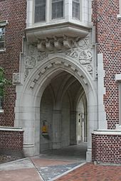Photo depicts an open pedestrian passageway through one wing of Sledd Hall, a red brick and carved stone student dormitory at the University of Florida, built in 1929 in the then-popular collegiate gothic architectural style