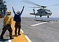 US Navy 040715-N-6920A-004 Airman Richard Juarez, from San Bernandino, Calif., signals the pilot of an MH-60S Knighthawk to lift off from USS Saipan (LHA 2).jpg