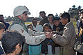 US Navy 050103-N-5386H-166 Steelworker 2nd Class Chad Larsen, assigned to Naval Mobile Construction Battalion Seventeen (NMCB-17), shakes the hand of Iraqi school children in the city of Haidiriyah, Iraq.jpg