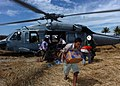 US Navy 050113-N-8629M-267 Tsunami victims anxiously grab relief supplies brought to them by a U.S. Navy MH-60S Knighthawk helicopter.jpg