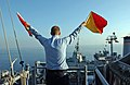 US Navy 051129-N-0685C-007 Quartermaster Seaman Ryan Ruona signals with semaphore flags during a replenishment at sea.jpg