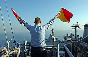 Flag semaphore - A US Navy crewman signals using flag semaphore during an underway replenishment exercise (2005)