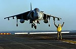 US Navy 051203-N-9866B-072 Aviation Boatswain's Mate 1st Class Roberto Gonzales directs an AV-8B Harrier as it lands on the flight deck of the amphibious assault ship USS Peleliu (LHA 5).jpg