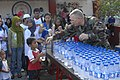 US Navy 071215-N-7286M-033 U.S. Air Force Chaplain, Maj. Philip G. Houser hands out water to the children at MEIN College.jpg