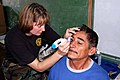 US Navy 090628-F-7885G-065 Cmdr. Dawn Clary, assigned to the U.S. Public Health Service and embarked aboard the Military Sealift Command hospital ship USNS Comfort (T-AH 20), examines a patient during a Continuing Promise 2009.jpg