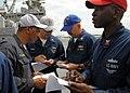 US Navy 100813-N-4649B-021 Sailors aboard the multipurpose amphibious assault ship USS Bataan (LHD 5) discuss life raft assignments during an abandon ship drill.jpg