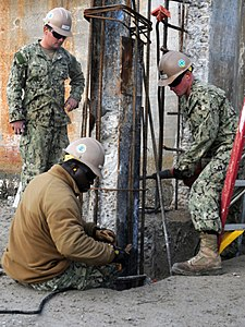US Navy 120131-N-IA881-005 Seabees with Naval Mobile Construction Battalion (NMCB) 74 reinforce pilings which will be used to support a boat ramp o.jpg