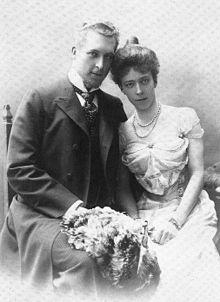 Albert et Élisabeth posent assis une gerbe de fleurs sur les genoux