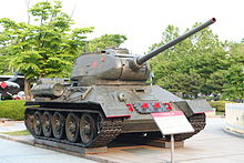 A large, heavily armed and armored tank outside a modern-day museum