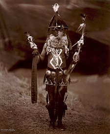 Navajo man in ceremonial dress with mask and body paint, c. 1904.