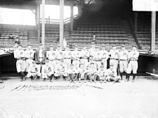 Black-and-white photo of 21 baseball players in two rows; the back row stands while the front row kneels