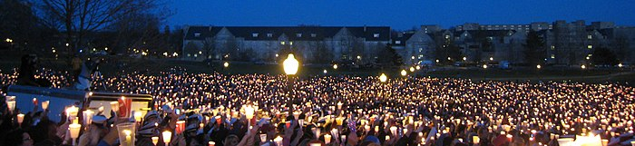 A sea of candles shining in the darkness of the Drillfield with campus buildings on the opposite side.