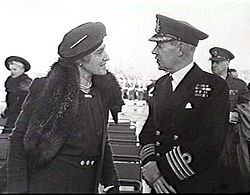 Woman in dark coat and hat talking with man in dark military uniform