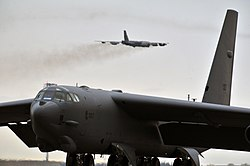 A B-52H Stratofortress of the 5th Bomb Wing sits on the flight-line as another B-52H takes off from Minot AFB.