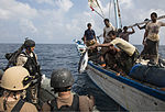 A Yemeni fisherman aboard a dhow gives a fish to U.S. Sailors assigned to the guided missile destroyer USS Mason (DDG 87) during a visit, board, search and seizure operation Nov. 21, 2013, in the Gulf of Aden 131121-N-PW661-023.jpg