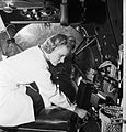 A female electrical worker fitting the bomb aimers switch into the half completed fuselage of an Avro Lancaster. D18193.jpg