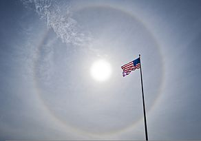 A solar halo illuminates the sky behind an American flag flying outside Building 1 at Eglin Air Force Base, Fla., in the early afternoon Nov. 12, 2013 131112-F-OC707-003.jpg