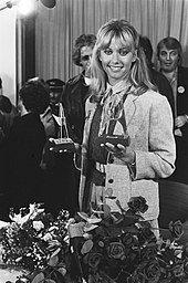 A woman with long blonde hair holding two trophies
