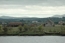 A collection of ruined farm buildings and a nissen hut sit amid fields that lie beyond the grey waters of a river. Wooded slopes and higher treeless hills lie beyond.