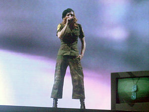 "American Life (song) - Madonna performing the first verse of ""American Life"" while standing on top of a structure made up of TV sets on the Re-Invention World Tour in 2004"