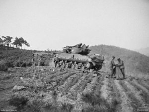 A main battle tank in a cultivated field. To the rear are two soldiers holding a map