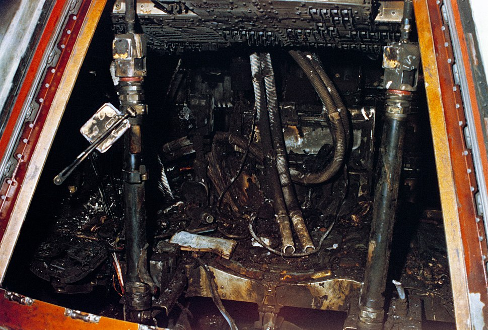 The inside of a small spaceship, charred and apparently destroyed.