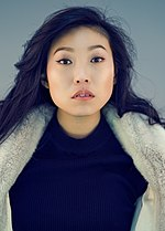 Awkwafina against a blue background, facing forward