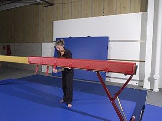 Mat (gymnastics) - This gymnastics coach is fastening a foam beam wrap to the balance beam.